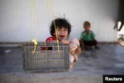 FILE - A Syrian refugee child reacts while sitting in a swing in Al Zaatari refugee camp, in the Jordanian city of Mafraq, near the border with Syria, September 19, 2015.