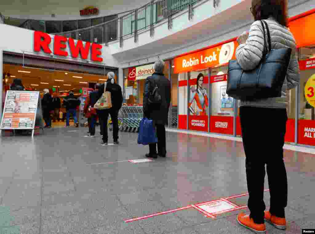 People wait to enter a store behind red lines that mark the distance people have to keep between them, at a Rewe grocery store in Potsdam, Germany.