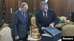 Menhan Rusia, Sergei Shoigu (kanan) menunjukkan kepada Presiden Rusia Vladimir Putin rekaman penerbagan pesawat pembom SU-24 yang ditembak jatuh Turki di Moskow, Rusia (8/12).