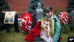 A woman holds a portrait of Joseph Stalin near the former Soviet leader's tomb near the Kremlin wall, as she came to mark the 136th anniversary of his birth, in Moscow, Russia, Dec. 21, 2015.