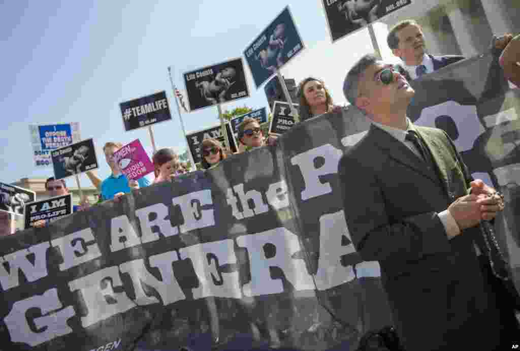 Michael Hichborn kneels and prays as he joins demonstrators while waiting for the Supreme Court decision on the Hobby Lobby case outside the Supreme Court, in Washington, June 30, 2014.