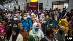 Para penumpang kereta api mengenakan masker sebagai pencegahan virus corona, di stasiun di Surabaya, 15 Maret 2020. (Foto: AFP)