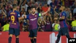 Lionel Messi (C) jubile avec ses co-équipiers Luis Suarez (G) et Arturo Vidal lors du match contre PSV, le 18 septembre 2018.