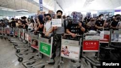 香港反送中抗议者2019年8月13日在香港国际机场站在用手推车组成的屏障后手举标语示威。