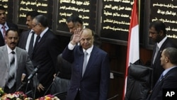 Yemen's President Abd-Rabbu Mansour Hadi waves as he arrives to the Parliament in Sana'a, Yemen.