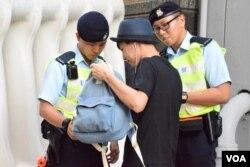 警員在灣仔保安區檢查途人的隨身背包。(美國之音湯惠芸)