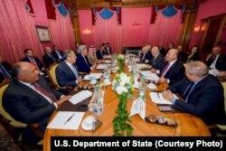 ລັດຖະມົນຕີການຕ່າງປະເທດ ສະຫະລັດ ທ່ານ John Kerry, ທີສາມຈາກຊ້າຍ, ນັ່ງກັບບັນດາລັດຖະ ມົນຕີການຕ່າງປະເທດ ຈາກ ອີຈິບ, ຣັດເຊຍ, ຊາອູດີ ອາເຣເບຍ, ກາຕ້າ, ອີຣັກ, ອີຣ່ານ, ທູດພິເສດອົງ ການສະຫະປະຊາຊາດ, ເທີກີ ແລະ ຈໍແດັນ ໃນເມືອງ ລໍຊານ, ປະເທດ ສວິດເຊີແລນ, ໃນຂະນະທີ່ກຸ່ມ ດັ່ງກ່າວປຶກສາຫາລືແນວຄິດສຳລັບການແກ້ໄຂບັນຫາ.