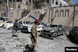 FILE - Houthi militants walk past damaged cars outside the Presidential Compound after it was hit by air strikes in Sana'a, Yemen, May 7, 2018.
