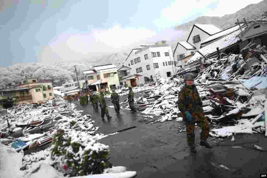 Члены сил обороны Японии проходят через заснеженные руины Камаиси, Япония, 16 марта 2011г.