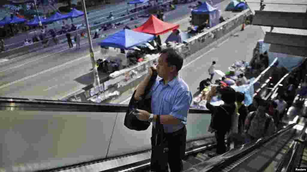 کارمندان دولتی صبح دوشنبه در حال رفتن به سر کار از کنار محوطه ای می گذرند که معترضان در خارج از مقر حکومت هنگ کنگ بست نشسته اند-- ۱۴ مهرماه ۱۳۹۳ (۶ اکتبر ۲۰۱۴)
