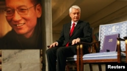 Chairman of the Norwegian Nobel Committee Thorbjoern Jagland looks down at the Nobel certificate and medal on the empty chair where this year's Nobel Peace Prize winner jailed Chinese dissident Liu Xiaobo would have sat, as a portrait of Liu is seen in th