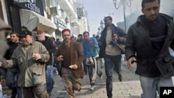 Protestors run away from tear gas during a demonstration against former Tunisian President Zine El Abidine Ben Ali in the center of Tunis, 17 Jan 2011