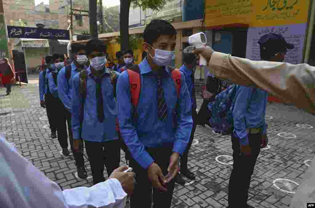 اسکول آنے والے طلبہ قطار میں کھڑے ہو کر اپنے جسم کا درجہ حرارت چیک کراتے رہے جس کے بعد ہی انہیں اندر جانے کی اجازت دی گئی۔