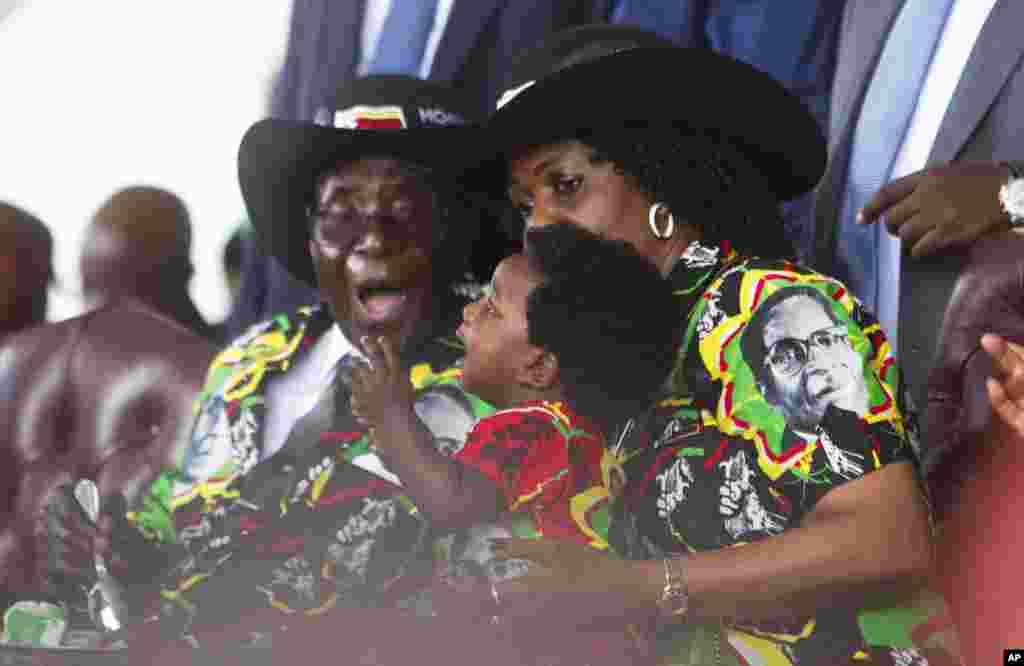 Le président zimbabwéen Robert Mugabe et sa femme Grace, à droite, ontemplent leur petit-fils lors de la célébration de 93 ans d'anniversaire du chef d'Etat du Zimbabwe à Matopos, dans la banlieue de Bulawayo, 25 février 2017.