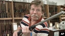 John Kinkade sostiene un rifle en la tienda de armas que administra en Iowa.