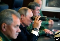 FILE - Russian President Vladimir Putin, center, Defense Minister Sergei Shoigu, left, and Chief of the General Staff of the Russian Armed Forces Valery Gerasimov, right, watch a military exercise at a training ground at the Luzhsky Range, near St. Petersburg.