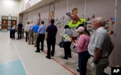 FILE - People line up to vote inside a precinct in Matthews, N.C., Tuesday, March 15, 2016.
