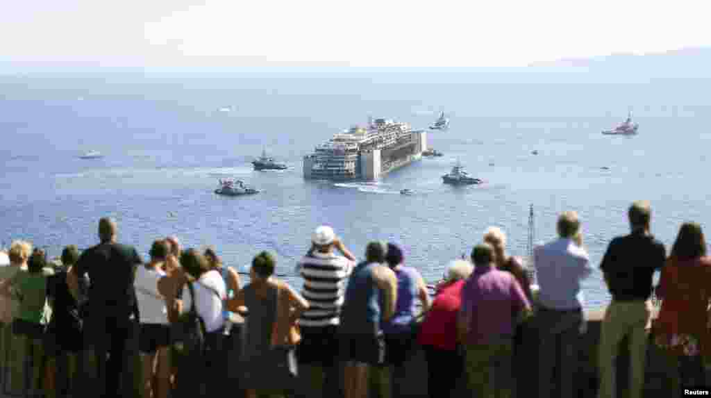 People watch the cruise liner Costa Concordia moving anticlockwise during the refloat operation maneuvers at Giglio Island, italy, July 23, 2014. A convoy of 14 vessels, led by the tug boat Blizzard, towed the Concordia to a port near Genoa in northern Italy where it is going to be broken up for scrap.