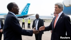 U.S. Secretary of State John Kerry (R) shakes hands with Democratic Republic of Congo Foreign Minister Raymond Tshibanda upon his arrival at N'djili Airport in Kinshasa, May 3, 2014.