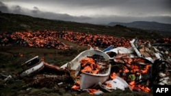 FILE - Wrecked boats and thousands of life jackets used by refugees and migrants during their journey across the Aegean sea lie in a dump in Mithimna, Greece, Feb. 19, 2016.