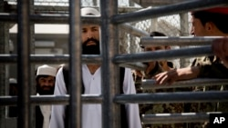 FILE - An Afghan prisoner waits in line for his release from Parwan Detention Facility, March 25, 2013.