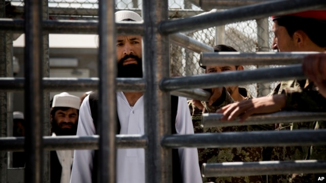 FILE - An Afghan prisoner waits in line for his release from Parwan Detention Facility after the U.S. military gave control of its last detention facility to Afghan authorities in Bagram, outside Kabul, Afghanistan, March 2013.