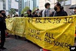 Aktivis prodemokrasi memegang spanduk saat mereka mengantre di luar pengadilan untuk mengikuti persidangan di Hong Kong pada hari Senin, 1 Maret 2021.