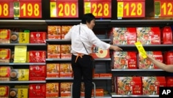 An employee stands on a stepladder as she stocks boxes of mooncakes at a supermarket in Beijing, Wednesday, Sept. 14, 2016.