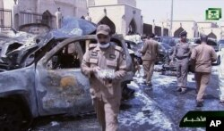 FILE - In this image taken from video provided by Saudi TV, burned-out cars are seen as investigators collect evidence in the aftermath of a suicide bomb outside the Imam Hussein mosque in the port city of Dammam, Saudi Arabia, May 29, 2015. The Islamic State group said one of its soldiers had carried out the attack.