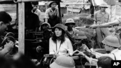 Jane Fonda ngồi trên nòng súng phòng không của quân đội Bắc Việt trong chuyến thăm Hà Nội năm 1972.