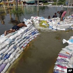 Soldiers use sand bags to build barriers in flooded Pathum Thani province, in Bangkok's suburbs October 20, 2011.