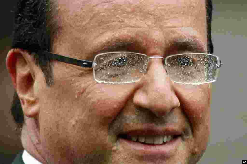 Ông Hollande tươi cười khi đi qua đại lộ Champs Elysees trong trời mưa. (AP)
