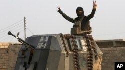 A member of Iraq's elite forces flashes a victory sign as forces advance toward Islamic State positions in the village of Tob Zawa, near Mosul, Iraq, Oct. 25, 2016.