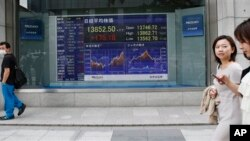 People walk by an electronic stock board of a securities firm in Tokyo Monday, July 1, 2013. Global stocks swung between gains and losses Monday after China's manufacturing weakened in June amid a credit crunch. Tokyo's Nikkei 225 rose 1.3 percent to 13,8