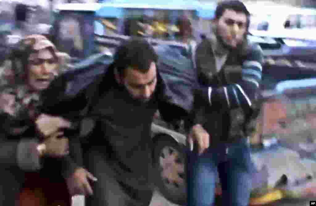 在政府军对叙利亚哈马郊外的哈尔法亚进行空袭后,叙利亚人帮助一位伤员