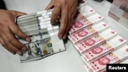 Chinese yuan and U.S. dollar banknotes being counted at a branch of Bank of China in Taiyuan, China, Jan. 4, 2016.