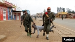 Congolese soldiers drag away a protester critical of the government's alleged inaction to address rising inter-ethnic tensions in the town of Butembo, in North Kivu province, DRC, Aug. 24, 2016.