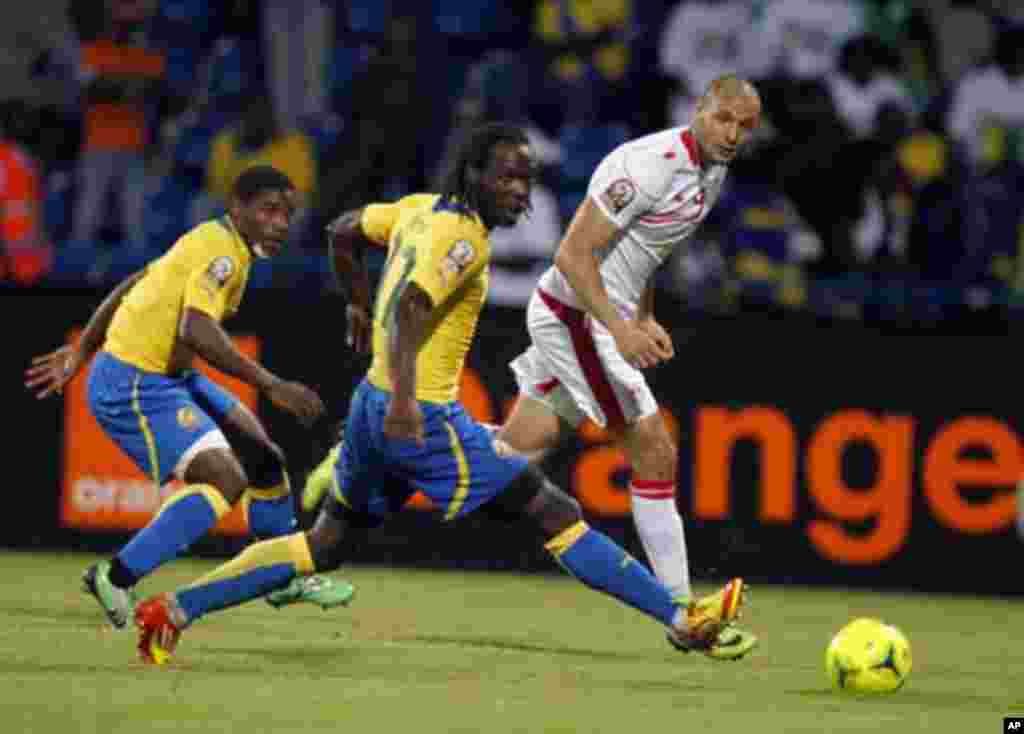 Tunisia's Yassine Chikaoui (R) challenges Eric Mouloungui (C) and Edmond Mouele of Gabon during their African Cup of Nations Group C soccer match at Franceville stadium in Gabon January 31, 2012.
