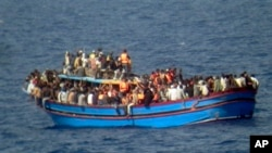 File - A boat overcrowded with migrants is pictured in the Mediterranean Sea. The bodies of some 30 would-be migrants were found in the hold of a packed smugglers' boat making its way to Italy, In this photo released by the Italian Navy, June 29, 2014.