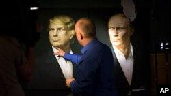 지난 9일 러시아 모스크바의 한 주점에서 기자가 미국 대선 개표 방송중계 화면에 나온 도널드 트럼프 당선인의 그림을 가리키고 있다. 오른쪽은 블라디미르 푸틴 러시아 대통령의 그림. (자료사진)