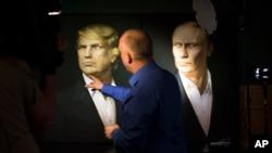 Seorang jurnalis menunjuk ke potret Donald Trump dan Vladimir Putin dalam acara siaran langsung pemilihan presiden di pub Union Jack di Moskow, Rusia (9/11). (AP/Alexander Zemlianichenko)
