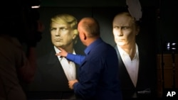 A journalist points at a portrait of U.S. President-elect Donald Trump, with a portrait of Russian President Vladimir Putin at right, at the Union Jack pub in Moscow, Russia, Nov. 9, 2016. The Trump campaign is denying it had contacts with Russian officials.