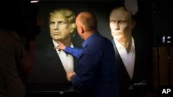2016年11月9日,一名俄羅斯記者用手指指著川普的畫像。右邊是普京總統的畫像。