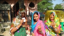 Residents of a low income settlement in Gurgaon, adjoining Delhi, hold up their fingers after voting, April 10, 2014. (Anjana Pasricha/VOA)