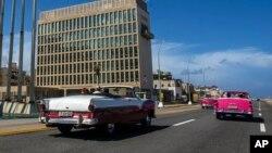 ARCHIVO- Turistas pasean en convertibles clásicos en el Malecón de La Habana frente al edificio de la Embajada de EE.UU. Octubre 3 de 2017. El Departamento de Estado informó que otro de sus empleados en la misión diplomática ha sido afectado por una misteriosa dolencia cuyo origen se desconoce.