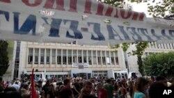 그리스 정부가 12일 헬레닉 방송사 잠정폐쇄를 발표한 후 아테네 본사 건물 앞에서 항의하는 시위대.