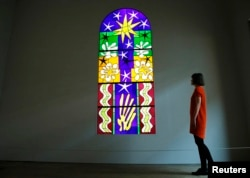 "An employee poses with a stained glass ""Christmas Eve"" (Nuit de Noel), designed by Henri Matisse, and in collaboration with Paul Bony, at the Tate Modern gallery in London, April 14, 2014."