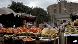 A fruit vendor checks an apple as he waits for customers in the Sayeda Zeinab neighborhood of Cairo, Egypt. Egyptians are cutting spending and trying to make it through the country's worst inflation in a decade under President Abdel-Fattah el-Sissi's economic reforms.