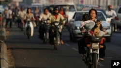 A local woman, foreground right, drives her motorbike as she carries her baby and a dog on a busy street in Phnom Penh, Cambodia, Tuesday, Feb. 18, 2014. (AP Photo/Heng Sinith)