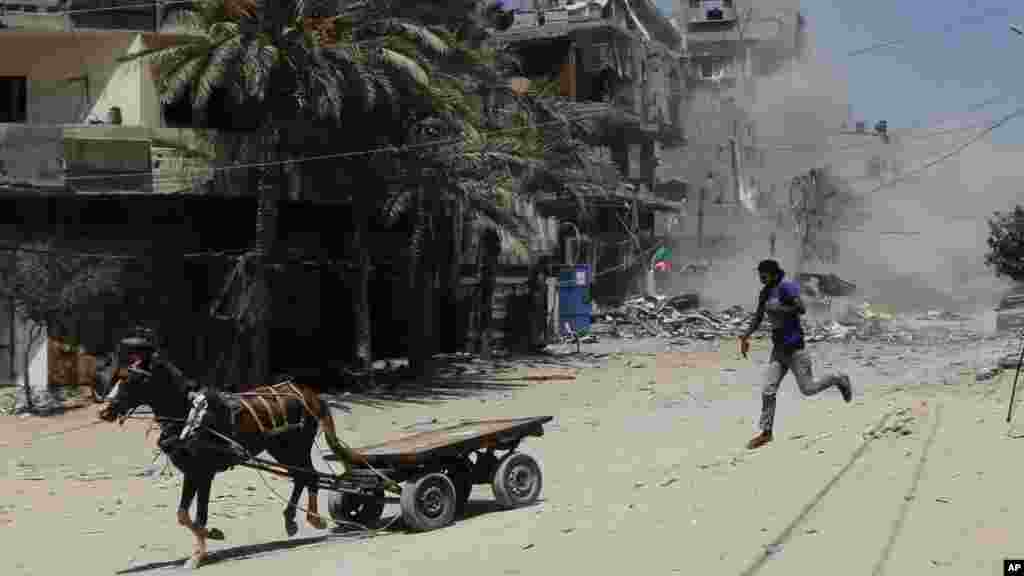 A Palestinian flees after an Israeli strike hits a three-story building belonging to the Abdul Hadi family in Gaza City in the northern Gaza Strip, Aug. 24, 2014.